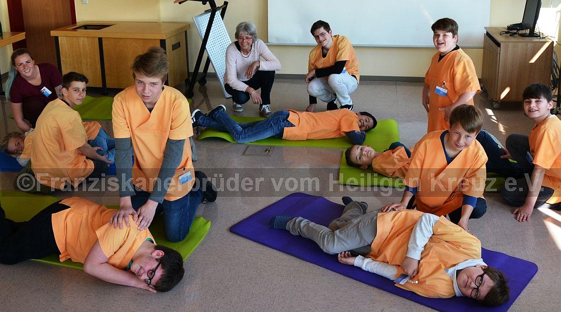 Angeleitet von Agnes Baumgärtner, Gesundheits- und Krankenpflegerin, (links) und Henrike Beier, Dipl. Medizinpädagogin, übten die Jungs die stabile Seitenlage im Medienraum St. Marienwörth