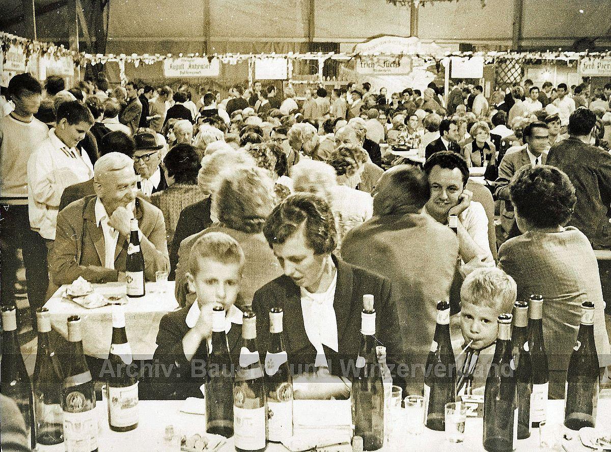 Während die Kinder ihre Limonade genießen, sprechen die erwachsenen Gäste lieber dem vergorenen Traubensaft zu: Ein Bilddokument aus dem Archiv des Bauern- und Winzerverbandes, das um 1970 durch einen leider unbekannten Fotografen aufgenommen wurde.