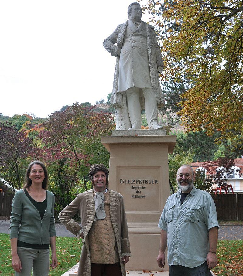 Der Schauspieler Prieger unterm Denkmal Prieger mit den Restauratoren Kirsten und Marcus Rebensburg.